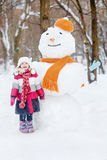 Little girl stands and sings in front of big snowman Royalty Free Stock Images