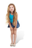 Little girl stands slightly bending forward Stock Images
