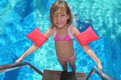 Little girl stands on stairs in pool Stock Image