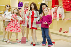 Little girl stands together with group of dressed mannequins Royalty Free Stock Photos