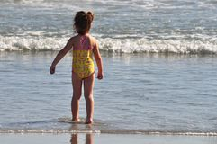 Little Girl Stands in Waves at Beach. Little girl in yellow swimsuit stands in the shallow waves at Florida beach royalty free stock photo