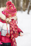 Little girl stands in winter park holding artificial bird Royalty Free Stock Photo
