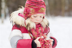 Little girl stands in winter park warming artificial bird Royalty Free Stock Image