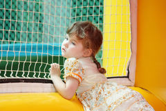 Little girl stands in yellow bouncy castle Stock Photos