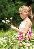 The little girl is stanging in the meadow Royalty Free Stock Photo