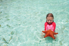 Little girl with a starfish Royalty Free Stock Photo