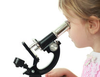 Little girl staring into black microscope Royalty Free Stock Photography