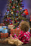Little girl staring at Christmas tree, vertical Stock Image