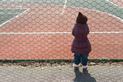 Little girl staring at the field throw metal mesh Royalty Free Stock Photo