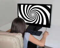 Little girl staring at  hypnosis spiral on the big screen of her computer. Royalty Free Stock Images