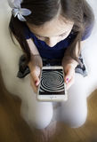 Little girl staring at  hypnosis spiral on her cell phone Stock Photo