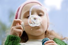 Little girl starts up soap bubbles Royalty Free Stock Images