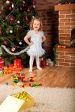 Little girl staying near Christmas tree Stock Photos