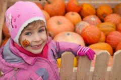 Little girl stays near box with pumpkin Stock Photos