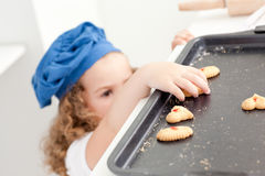 Little girl stealing cookies Stock Photos