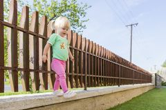 A little girl steals from the edge of a fence. Stock Images