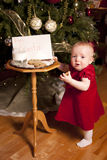 Little girl steals Santa cookie Stock Images