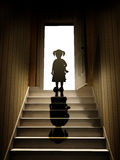 Little girl on steps leading from a dark basement to open the do Royalty Free Stock Photography