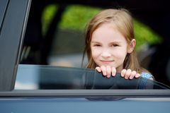 A little girl is sticking her head out the car window Stock Photo