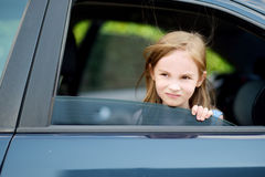 Little girl sticking her head out the car window Stock Images