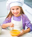Little girl stirs cookie dough Royalty Free Stock Photo
