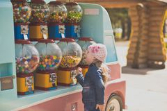 Portrait of a girl in the Park on a walk. The little girl stopped in front of a battery of machines for the sale of small sweets. Genuinely enjoys opportunities Royalty Free Stock Photography