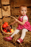 Little girl on straw with a basket of fruit Royalty Free Stock Images
