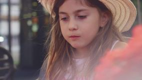 Little girl with straw hat eating her sandwich and playing with balloon. Little girl with straw hat eating her cheeseburger and playing with balloon stock footage