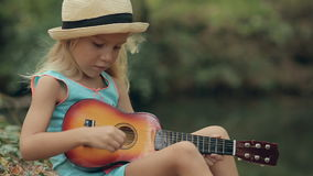 Little girl in a straw hat sitting in the forest stock footage