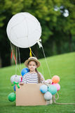 Little girl in straw hat sitting in toy hot air balloon while playing in park Royalty Free Stock Photography