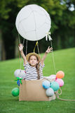 Little girl in straw hat sitting in toy hot air balloon while playing in park Stock Photos