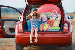 Little girl in straw hat sitting in the trunk of a car. Little girl , brunette with long curly hair , dressed in a striped sailor's shirt , dark sunglasses and a Royalty Free Stock Photography