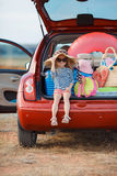 Little girl in straw hat sitting in the trunk of a car Stock Photo