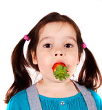 Little girl with Strawberry in mouth Royalty Free Stock Image