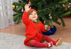 The little girl in the Strawberry suit with the raised hand sits about a New Year tree.  royalty free stock image