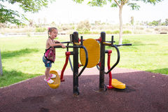 Little girl on street exercise machines Stock Image