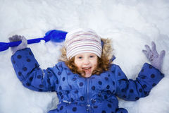 Little girl stretches her hand to catch falling snowflakes. Wint Stock Photography