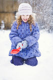 Little girl stretches her hand to catch falling snowflakes. Wint Stock Photos