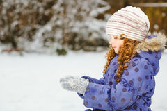 Little girl stretches her hand to catch falling snowflakes. Wint Stock Photo