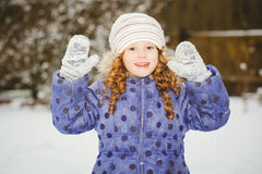 Little girl stretches her hand to catch falling snowflakes. Wint Royalty Free Stock Photography