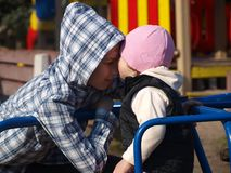 Little girl stretches to kiss her teen brother while sitting on the carousel stock image