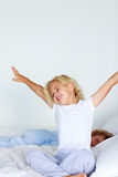 Little girl stretching in bed Royalty Free Stock Photography