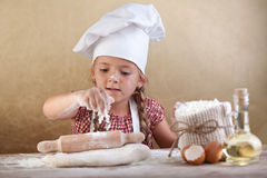 Little girl stretching the cookie dough Stock Photos