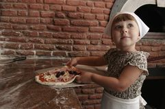 Little girl stretching the pizza up the shovel. Royalty Free Stock Photography