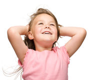 Little girl is stretching and rising hands up Stock Images