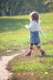 Little girl striding purposefully in the park Stock Photos