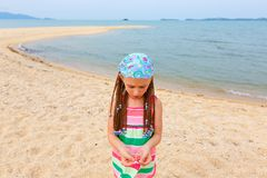 Little girl in a striped dress playing with sand on the beach stock photography