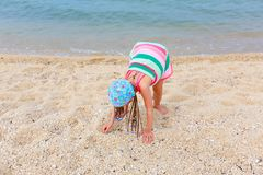 Little girl in a striped dress playing with sand on the beach. royalty free stock photo