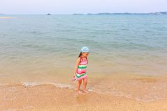 Little girl in a striped dress walks along the beach on a sunny afternoon. stock image