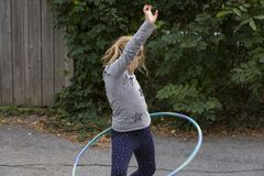 Little girl twisting her hips while playing with her hula hoop. Little girl in striped shirt and leggings twisting her hips while playing with her hula hoop in Stock Photos